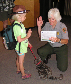 A new National Park Junior Ranger being sworn in; she is complete with her backpack and a (stuffed) cat that has joined her.